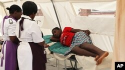 A woman is attended to after suffering from a suspected case of typhoid at a local hospital in Harare, January 31, 2012.