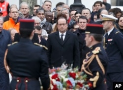 France's President Francois Hollande, left, and Prime Minister Manuel Valls, right, lay a wreath of flowers at Place de la Republique in Paris during a ceremony to honor the victims of the Islamic extremist attacks, Jan. 10, 2016.