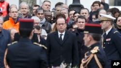 Presiden Perancis Francois Hollande, kiri, dan Perdana Menteri Manuel Valls, kanan, meletakkan karangan bunga saat upacara peringatan korban serangan di Place de la Republique, Paris, 10 Januari 2016.