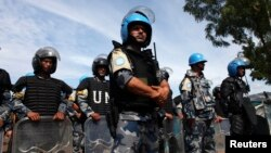 FILE - U.N. peacekeepers stand guard during a visit by U.N. Secretary-General Ban Ki-moon to an internally displaced persons camp at an UNMISS base in Juba May 6, 2014. Kenya announced Wednesday it will immediately pull its 1,000 troops out of South Sudan.