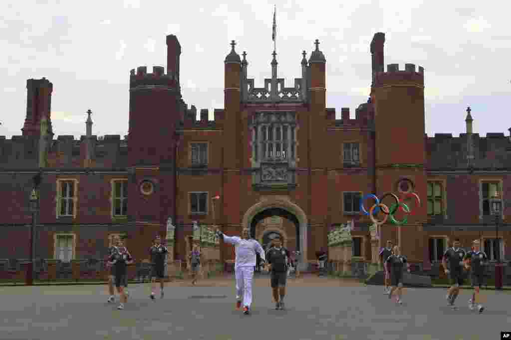 Four-time Olympic rowing gold medallist Matthew Pinsent runs through Hampton Court Palace in London with the Olympic Torch, July 27, 2012.