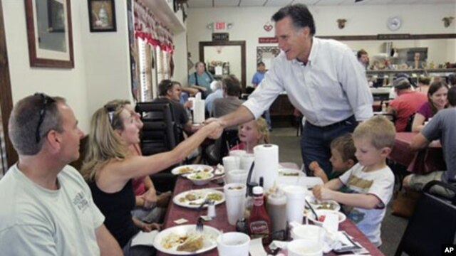 Former Massachusetts Gov. Mitt Romney shakes hands with people at Farm Boys restaurant during a visit in Chapin, S.C. Republican presidential frontrunner Romney is heading to Iowa on Friday for the first time this year, May 21, 2011