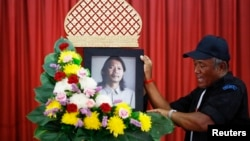 A man places a portrait of Kamol Duangphasuk, who was killed a day before, as his body is prepared for a funeral at a Buddhist temple in Bangkok, Apr. 24, 2014.