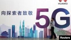一名男子走过在北京举办的中国国际信息通信展览会的一块华为公司5G技术广告牌。(2018年9月26日)