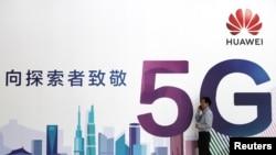 一名男子走過在北京舉辦的中國國際信息通信展覽會的一塊華為公司5G技術廣告牌。(2018年9月26日)