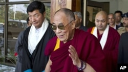 Tibetan spiritual leader the Dalai Lama, center, gestures after being received by the newly-elected Prime Minister of the Tibetan government-in-exile, Lobsang Sangay, left, as he arrives at the Kangra airport near Dharmsala, India, Sunday, Nov. 13, 2011.