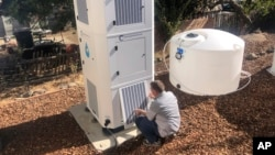 Ted Bowman, design engineer with Tsunami Products, installs a unit in homeowner Don Johnson's backyard in Benicia, Calif., Sept. 28, 2021. The recent invention can make water out of the air and in parched California, some homeowners are already buying the devices. (AP Photo)