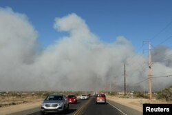 Cars flee the North Fire near Phelan, California, July 17, 2015