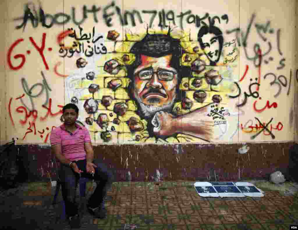 A protester, opposing Egypt's President Mohamed Morsi, sits next to graffiti depicting Morsi on a wall in Cairo July 2, 2013.