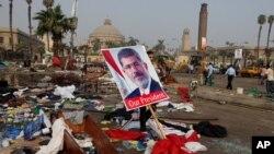 Seorang warga Mesir membawa poster Presiden terguling Mohammed Morsi di antara sisa-sisa kamp protes di Lapangan Nahda, Giza, Kairo, Mesir (15/8).