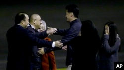 Kenneth Bae, second from left, who had been held in North Korea since 2012, is greeted after arriving at Joint Base Lewis-McChord, Washington, Nov. 8, 2014.