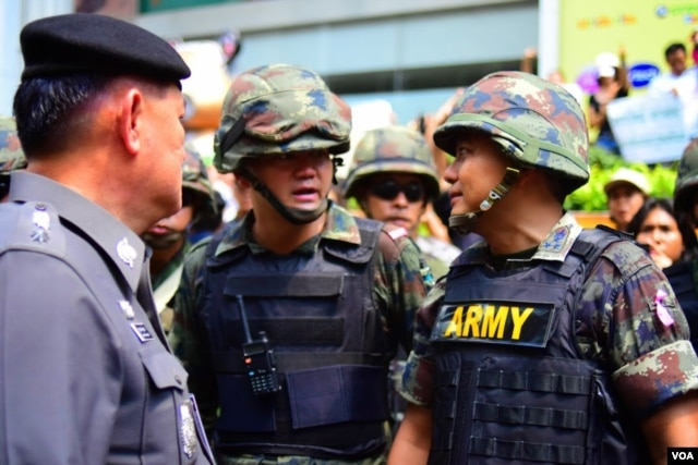 Soldiers and police discuss how to handle a growing crowd of anti-coup protestors in front of a McDonald's restaurant in Bangkok, May 25, 2014. (Steve Herman/VOA)