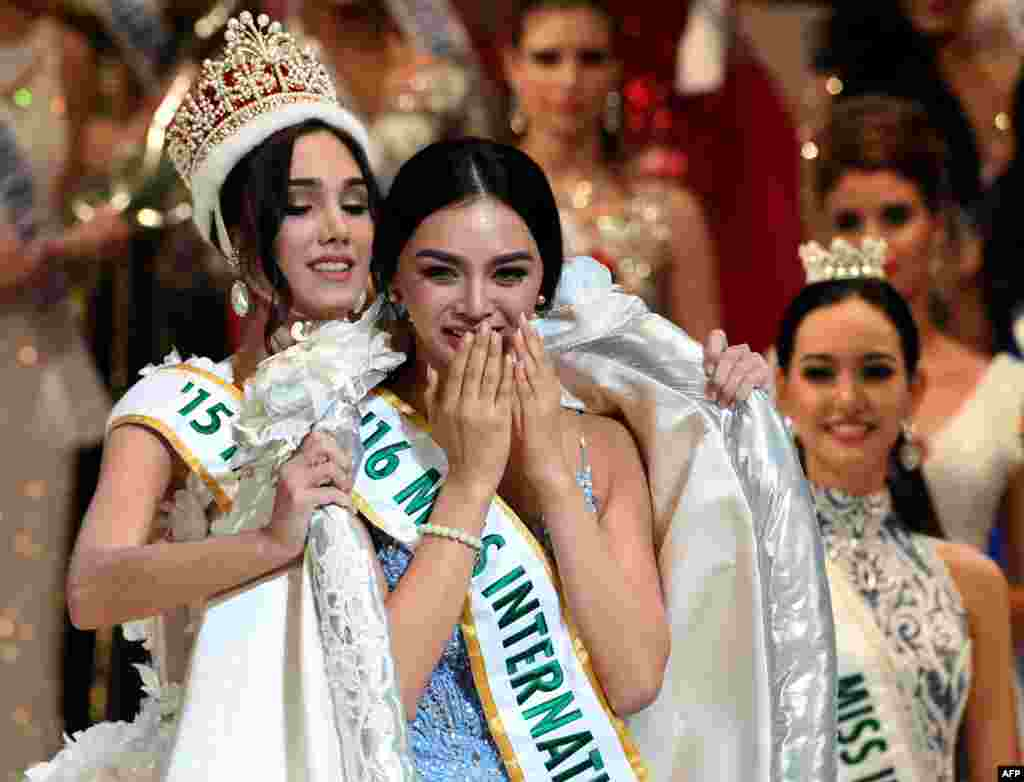 Newly elected 2016 Miss International Kylie Verzosa from Philippines (C) receives her gown from 2015 Miss International Edymar Martinez from Venezuela (L) during the Miss International beauty pageant final in Tokyo, Japan.