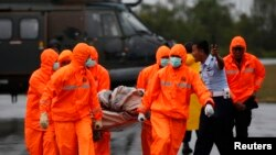 Lực lượng tìm kiếm và cứu hộ khiêng một bộ phận của xác máy bay AirAsia tìm được tại căn cứ không quân ở Pangkalan Bun, ngày 4/1/2015.