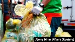 Seorang pekerja memegang kantong sampah medis untuk diangkut ke truk di Jakarta, 12 Agustus 2020. (Foto: Reuters/Ajeng Dinar Ulfiana)