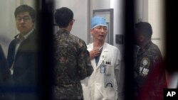 FILE - South Korean army soldiers talks with a medical doctor as he prepares to treat an unidentified injured person, unseen, believed to be a North Korean soldier, at a hospital in Suwon, South Korea, Nov. 13, 2017.