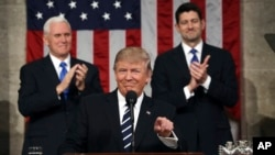 U.S. President Donald Trump, flanked by Vice President Mike Pence and House Speaker Paul Ryan of Wisconsin, gestures on Capitol Hill in Washington before his address to a joint session of Congress, Feb. 28, 2017.