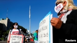 "Seorang demonstran menunjukkan poster bertuliskan ""karantina tanpa kelaparan"" dalam unjuk rasa menuntut bantuan bagi kelompok rentan di tengah penguncian akibat wabah virus corona, di Buenos Aires, Argentina, 13 Mei 2020. (Foto: Reuters)"