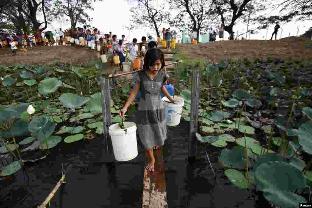 People line up to collect water at Yazarthingyan lake in Dala township, near Rangoon, Burma, since the inland lakes have all dried up in hot summer.