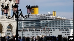 In this file photo, a cruise ship passes by St. Mark's Square filled with tourists, in Venice, Italy, Sunday, June 2, 2019. (AP Photo/Luca Bruno)