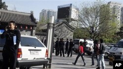 Police officers watch over an area where members of an underground church had planned to gather for worship in Beijing, China, April 17, 2011