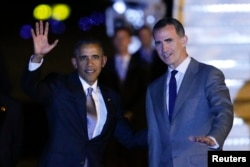 U.S. President Barack Obama, left, waves as is welcomed by Spain's King Felipe following his arrival aboard Air Force One at the Torrejon airbase, outside Madrid, Spain, July 9, 2016.