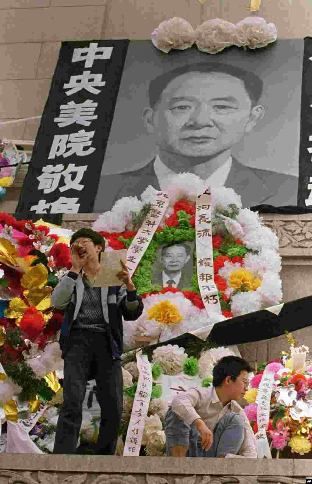"""中国学生在北京天安门广场上的人民英雄纪念碑前展示胡耀邦像和""""何处招魂""""""""民主之光耀邦""""等标语(1989年4月19日) 。1989年4月15日,抑郁中的胡耀邦突然心梗病逝,引发民众不满和自发悼念,直接触发后来的八九民运和""""六四事件""""。而这也导致胡耀邦多年来成为中共党内的禁忌,直到团派出身的前总书记胡锦涛任内才逐渐解禁,并于2015年11月20日为他举办百岁诞辰座谈会。"""