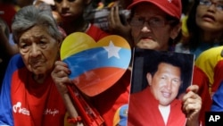 A woman holds a picture of Venezuela's President Hugo Chavez as supporters gather at Simon Bolivar square in Caracas,Venezuela, December 9, 2012.
