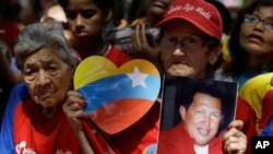 A woman holds a picture of Venezuela's President Hugo Chavez as supporters gather at Simon Bolivar square in Caracas,Venezuela, Dec. 9, 2012.