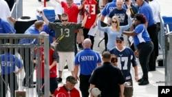 Aficionados al fútbol americano son revisados al ingresar al estadio Raymond James antes del partido entre Tampa Bay Buccaneers y Dallas Cowboys, el domingo, 15 de noviembre de 2015, en Tampa, Florida.