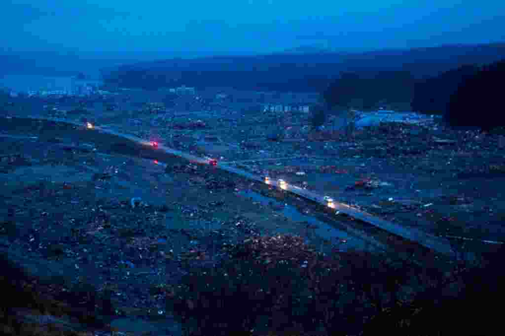 Japanese vehicles pass through the ruins of the leveled city of Minamisanriku, northeastern Japan, Tuesday March 15. (AP)