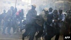 Антиправительственные демонстранты в Дакаре пытаются избежать вдыхания слезоточивого газа, февраль 2012 г.