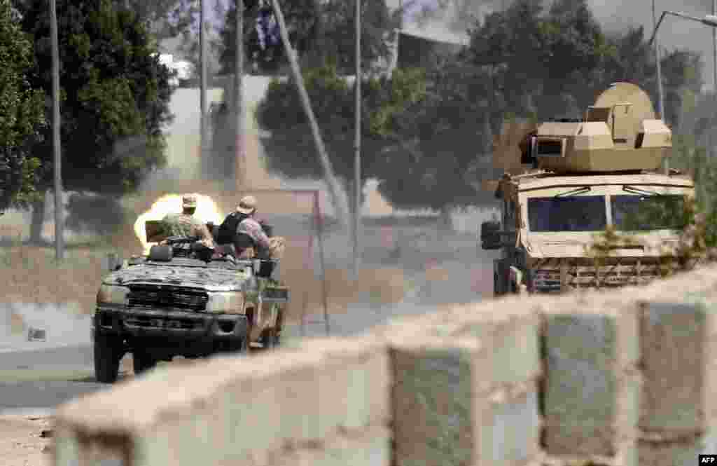 Fighters loyal to the internationally-recognized Government of National Accord (GNA) fire a jeep-mounted gun during clashes with forces loyal to Khalifa Haftar, leader of the dissident Libyan National Army, in Espiaa, about 40 kilometres south of the Libyan capital, Tripoli.