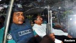 FILE - Mohammad Kamaruzzaman, center, assistant secretary general of the Jamaat-e-Islami party, sits inside a police van.