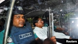 FILE - Mohammad Kamaruzzaman, center, of the Jamaat-e-Islami party sits inside a police van after hearing the verdict of his trial in Dhaka, May 9, 2013.