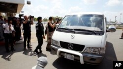 A van drives four refugees from Australia out of Phnom Penh International Airport, in Phnom Penh, Cambodia, Thursday, June 4, 2015. (AP Photo/Heng Sinith)