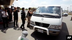 A van carries four refugees from Phnom Penh International Airport on June 4, 2015. They were part of an earlier refugee deal with Australia.