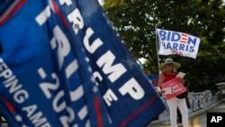 Người ủng hộ Tổng thống Donald Trump và cựu Phó Tổng thống Joe Biden vẫy cờ và biển bên ngoài một điểm bầu cử sớm tổng thống Mỹ. Số lượng cử tri họ Nguyễn dẫn đầu trong số những người dân Mỹ bỏ phiếu sớm cho kỳ bầu cử này ở hạt Harris lớn nhất của Texas.