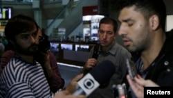 David Miranda (phải) trả lời báo giới sau khi đến sân bay quốc tế Rio de Janeiro, Brazil, hôm Chủ nhật. Ðứng giữa là nhà báo Mỹ Glenn Greenwald.