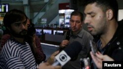 El periodista estadounidense Glenn Greenwald al centro en la foto observa a su pareja, David Miranda a la derecha en la foto, quien habla con los medios de prensa a su llegada a Río de Janeiro tras haber sido detenido en Londres.