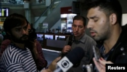 U.S. journalist Glenn Greenwald (C) looks on as his partner David Miranda (R) talks with the media after arriving at Rio de Janeiro's International Airport, August 19, 2013.