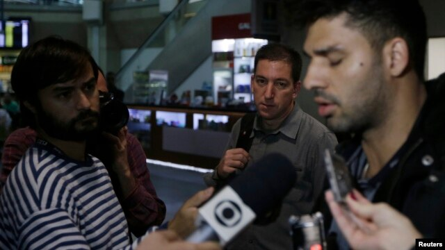 U.S. journalist Glenn Greenwald (C) looks on as his partner David Miranda (R) talks with the media after arriving at Rio de Janeiro's International Airport, Brazil, Aug. 19, 2013.