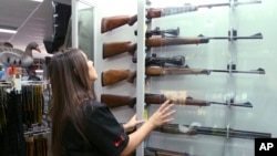 Salesperson Lauren Ungari checks rifles in a display in a gun shop in Sydney, Australia, Oct. 4, 2017. Australia recently concluded a three-month gun amnesty period that collected more than 51,000 guns.