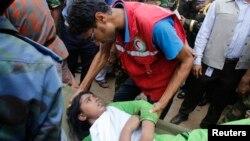 孟加拉建築坍塌造成嚴重傷亡﹐救護人員正為一名受傷工人。