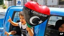 내전의 와중 리비아 수도 트리폴리의 비교적 안전한 지역에서 한 가족이 차를 타고 달리며 승리의 기쁨을 표현하고 있다.