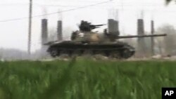 This image made from amateur video and released by Shaam News Network March 26, 2012, purports to show a Syrian military tank in Deir el-Zour, Syria.
