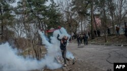 Seorang migran melemparkan tabung gas kembali ke arah polisi Yunani di zona penyangga perbatasan Turki-Yunani, dekat gerbang penyeberangan Pazarkule di Edirne, Turki, 4 Maret 2020.