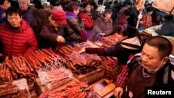 置办年货的北京市民在超市的腊肉腊肠摊位前选购。(2020年1月16日)
