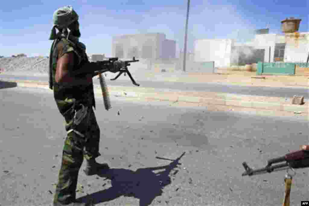 Libya fighter fire his machine gun at a Moammar Gadhafi political office next to a police station as they take control of Moammar Gadhafi loyalists villages in the desert some 730 kms south of Tripoli, at Mahruga, 50 kms north of the southern city of Sebb