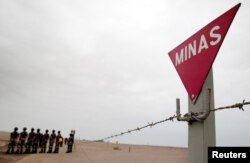 FILE - Chilean army mine sweepers stand next to a mine field during a demonstration of the removal of land mines at the Chacalluta Airport in Arica, northern Chile, Aug. 3, 2004.